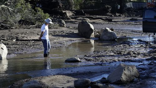 A man stands in flooded waters in Montecito on Wednesday. (AAP)