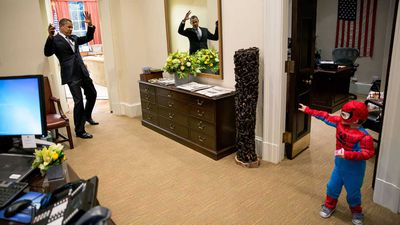 President Obama plays with a boy dressed as Spider-Man.