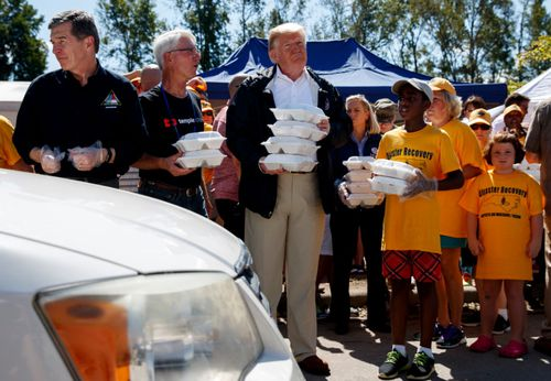 US President Donald Trump helps with flood relief supplies in North Carolina.