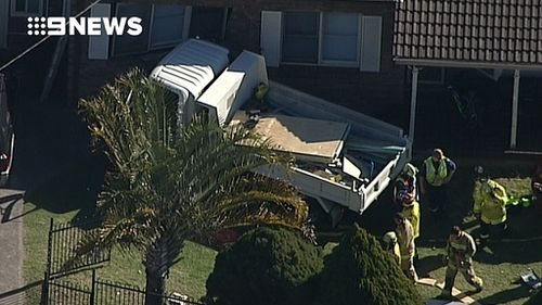 The truck hit a pedestrian before crashing into a house. (9NEWS)