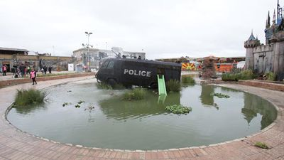 An armoured police van sits in a man-made lake. (AAP)