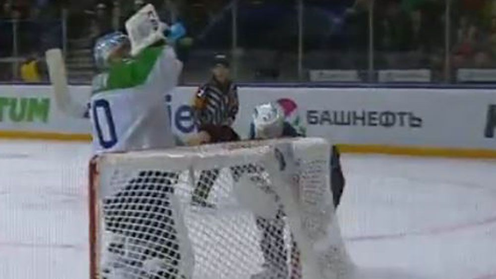 Ice hockey goalie takes a drink as play goes on around him
