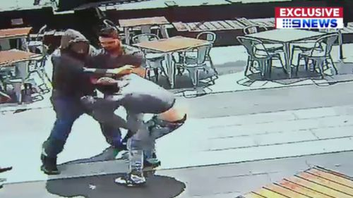 The taller, hooded man can be seen punching his victim. (9NEWS)
