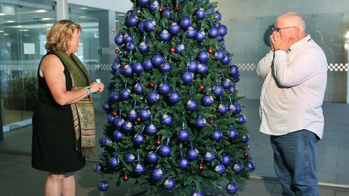 Leanne and Ronan Hume place a bauble for their son Sam who died in a road accident last year. (AAP)