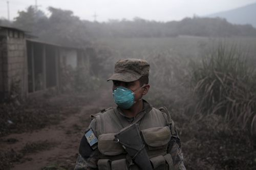 A soldier stands guard at a search and rescue sight near the Fuego volcano. Picture: AAP