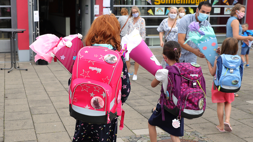 OBERPLEIS, GERMANY - AUGUST 13: First graders arrive with goodie bags for their first introductory day to school during the coronavirus pandemic on August 13, 2020 in Oberpleis near Bonn, Germany.