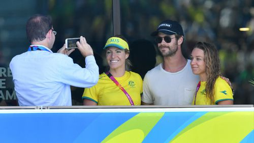 Hemsworth (centre) is seen posing for a photograph with Australian swimmers Emily Seebohm (left) and Tessa Wallace (right) during the heats. (AAP)