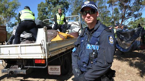 """Police remove protester's belongings during a raid at an Aboriginal """"tent embassy"""" in Perth in 2012. (AAP)"""