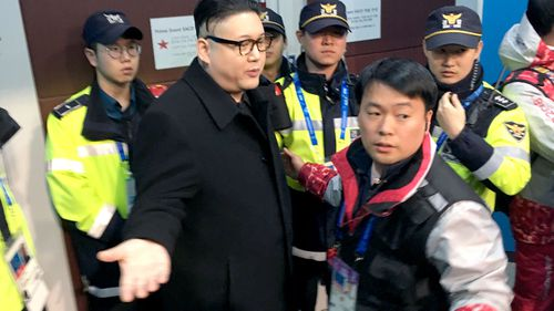 Police officers stand around the Kim Jong Un impersonator. (AAP)