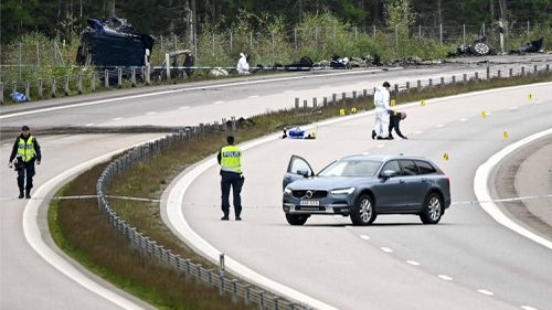 Forensic technicians work at the scene of the traffic accident that killed Swedish artist Lars Vilks