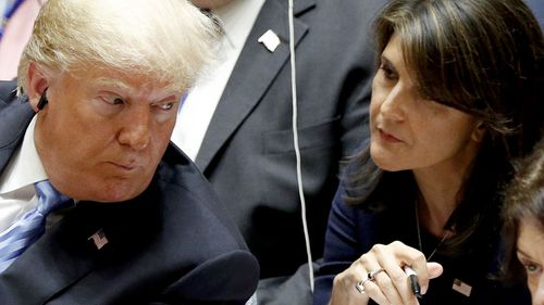 US Ambassador to the UN Nikki Haley shows US President Donald Trump a note as he chairs a United Nations Security Council meeting.