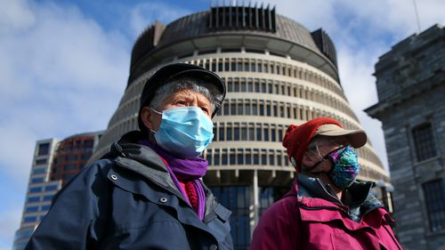 Two people in masks walk past the Beehive, New Zealand's parliament building in Wellington.