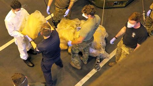 Sailors from HMS Dragon unload the drugs found on the dhow.