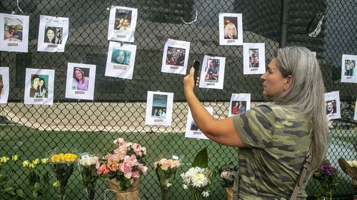 Photos of missing people are posted on a fence near the site of the Champlain Towers South Condo after the building collapsed.