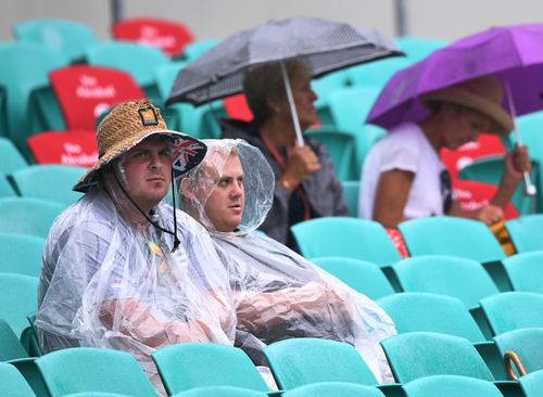 Spectators sit in the stands during rainfall on day one of the fifth test. (AAP)