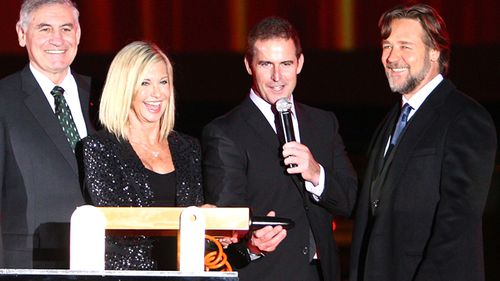 CEO of Echo Entertainment Larry Mullin (holding microphone), stands with Olivia Newton John and Russell Crowe (right) at the opening of 'The Star' in Sydney. (AAP)