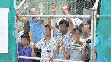 A March 21, 2014 file image of Asylum seekers staring at media from behind a fence at the Manus Island detention centre, Papua New Guinea. (AFP)