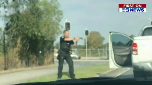 A police officer points his gun at the accused. Picture: 9NEWS