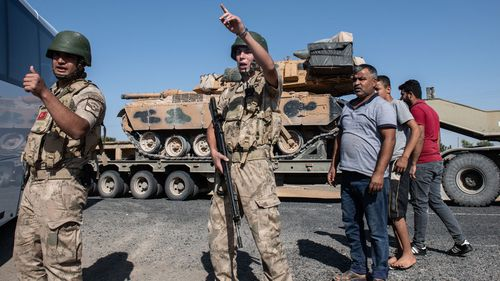 Turkish soldiers secure the area as Turkish military vehicles carry tanks to the Syrian border in Akcakale, Turkey.