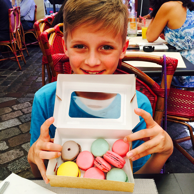 Child holding a box of macarons in France