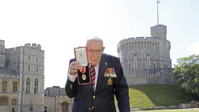 Captain Sir Thomas Moore poses after being awarded with the insignia of Knight Bachelor by Queen Elizabeth II at Windsor Castle on July 17, 2020 in Windsor, England.