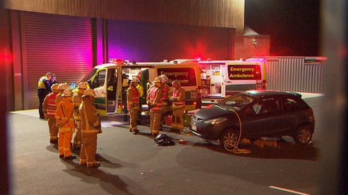 Paramedics treat the man who was trapped under the car. Picture: 9News