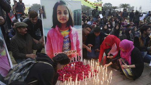 Pakistani students light candles during a protest rally to condemn the rape and killing of Zainab Ansari. (AAP)