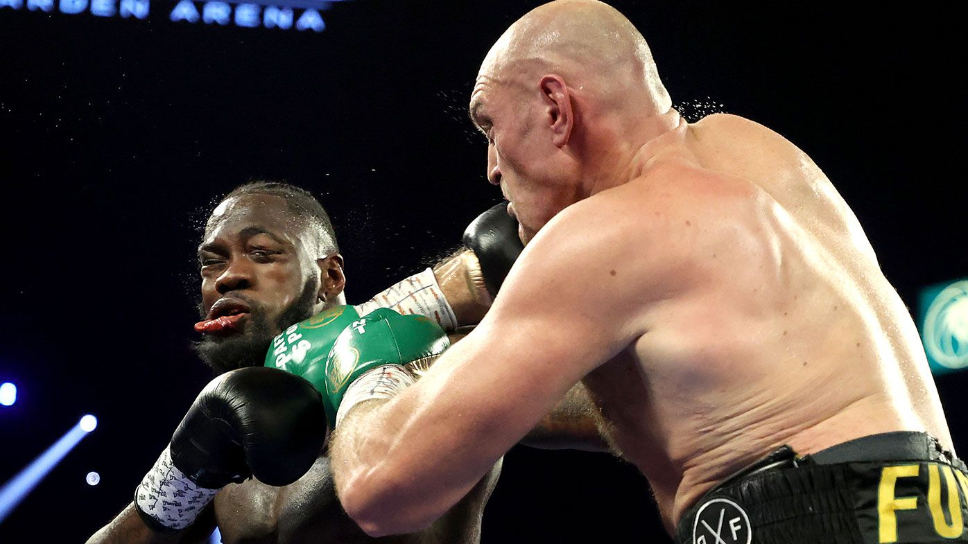 Tyson Fury (R) punches Deontay Wilder during their Heavyweight bout for Wilder's WBC and Fury's lineal heavyweight title