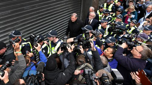 Circled by police, Cardinal Pell walked with his head down towards his lawyers office.