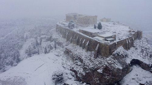In Athens, rare snow blankets the Acropolis, halts coronavirus vaccinations