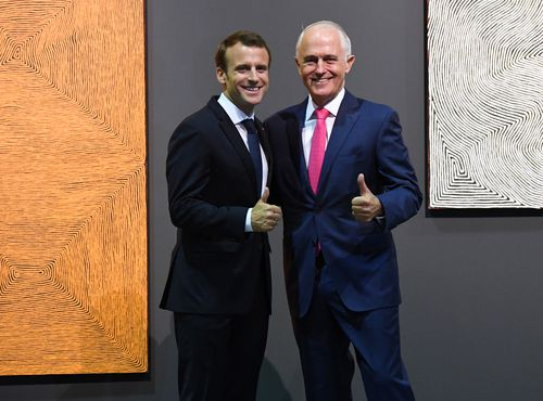The pair guive cameras the thumbs up in front of paintings by Australian artist George Tjungurrayi. (AAP)