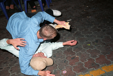 Drunk revellers wrestle in the street in Ibiza.