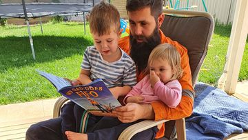 Craig Tarca, pictured with his son Charlie and daughter Ellen on the day before he left in March. He is reading a FIFO book explaining why he will be away for an extra long time.