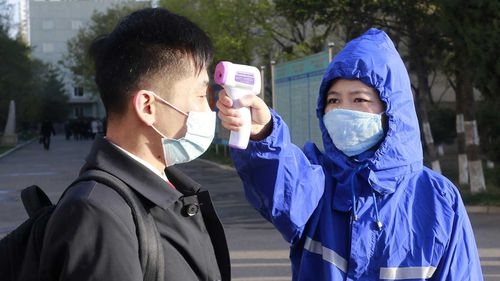 A man in Pyongyang, North Korea, gets his temperature checked as part of a coronavirus control measure.