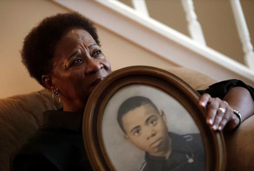Eberlene King poses with a photograph of her brother William Roy Prather when he was about 15-years-old at her home