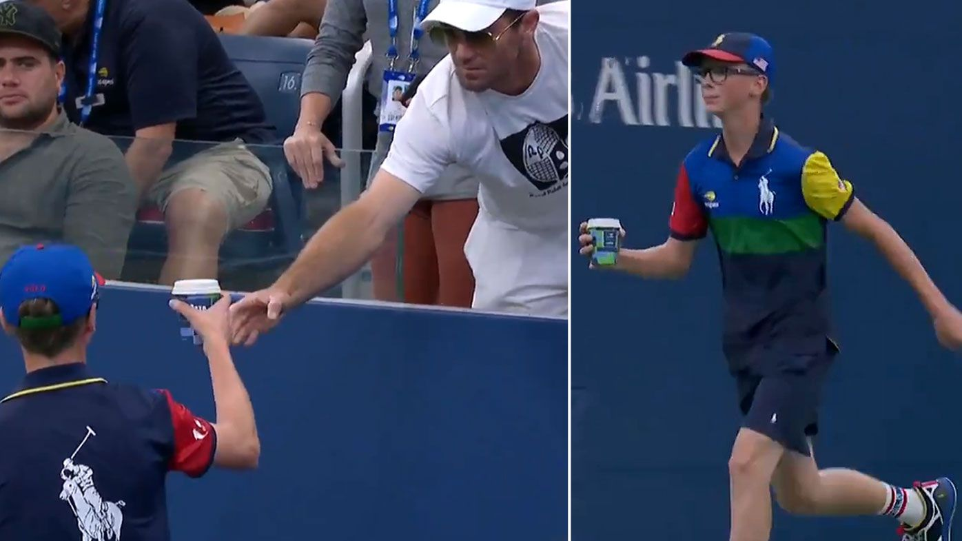 Venus Williams' coach hands a coffee to a ball boy to deliver to the tennis star