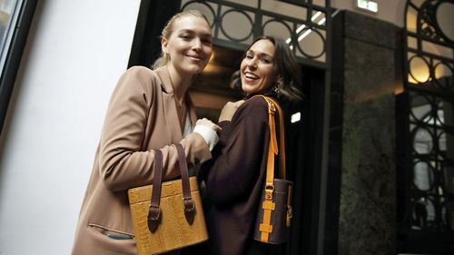 Model Arizona Muse, left, is flanked by designer and Officina del Poggio owner Allison Hoeltzel Savini as they present a creation of the Officina del Poggio women's Fall-Winter 2019-2020 collection, in Milan, Italy (Photo: Feb 2019)