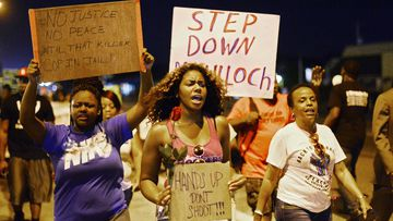 Demonstrators protest the shooting death of Michael Brown in Ferguson, Missouri.