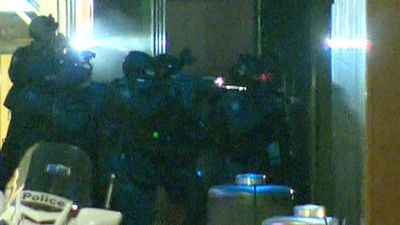 Moments later police shattered the glass door and stormed into the cafe. (9NEWS)