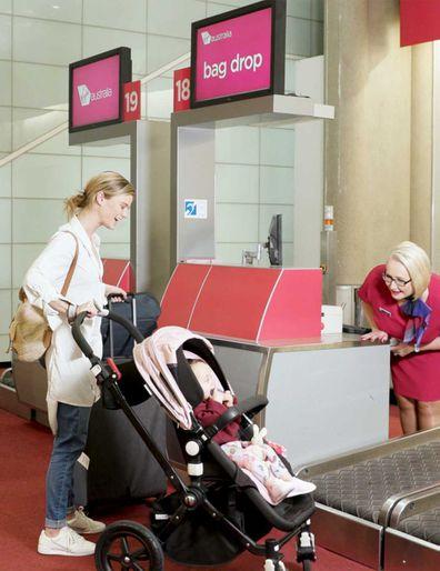 Mum and baby in pram at the Virgin Australia bag drop counter