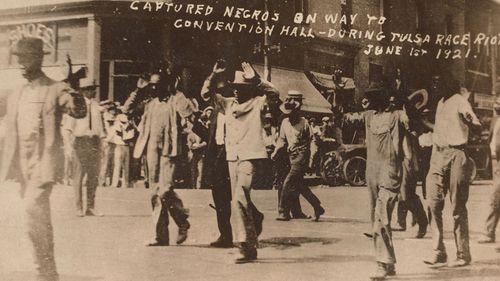 Men walk with their hands raised during the Tulsa massacre on June 1, 1921. Image is the gift of Cassandra P. Johnson Smith