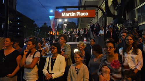 Members of the public gather at a ceremony to commemorate the first anniversary of the Lindt Café siege at Martin Place in Sydney. (AAP)