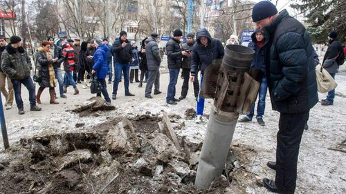 People look at a missile embedded in the street after a shelling. (Getty)