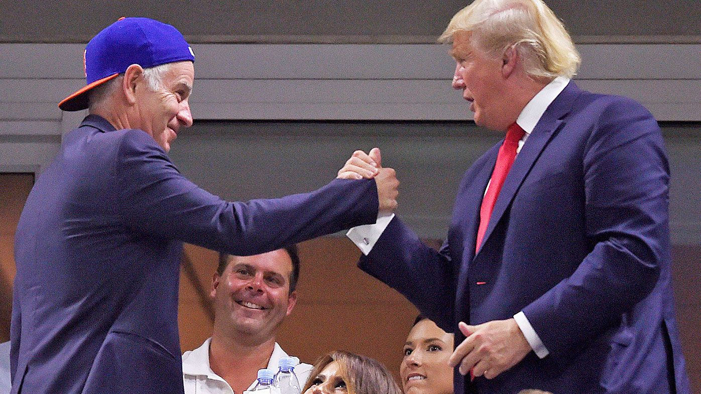 Republican presidential hopeful Donald Trump (R) shakes hands with US teennia great John McEnroe
