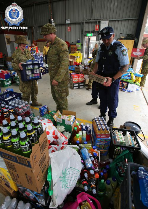 Officers from South Coast Police District and the Australian Defence Force load supplies into trucks. The supplies were delivered to the Milton Showground to support bushfire-affected towns on the state's South Coast.