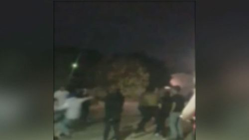 Vision shows a group of teenagers and young adults throwing punches and kicking one another. (9NEWS)