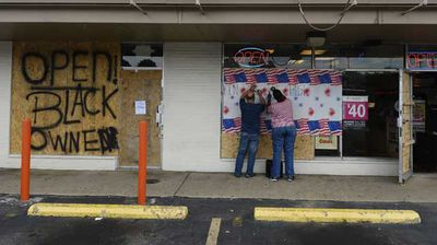 After several acts of looting, this boarded up shop specifies they are open and 'black owned'. (AP)