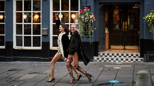 Two women walk past The Beehive pub following last orders at 6pm on October 9, 2020 in Edinburgh, Scotland. Pubs and restaurants in the central belt of Scotland close their doors for a fortnight while from 6pm in tough new coronavirus measures set out by the Scottish Government.
