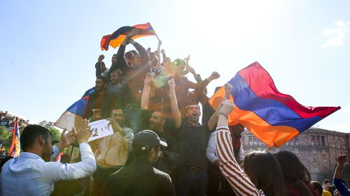 People wave the Armenian national flag as they celebrate Armenian Prime Minister's Serzh Sargsyan's resignation in Republic Square in Yerevan, Armenia. (AAP)