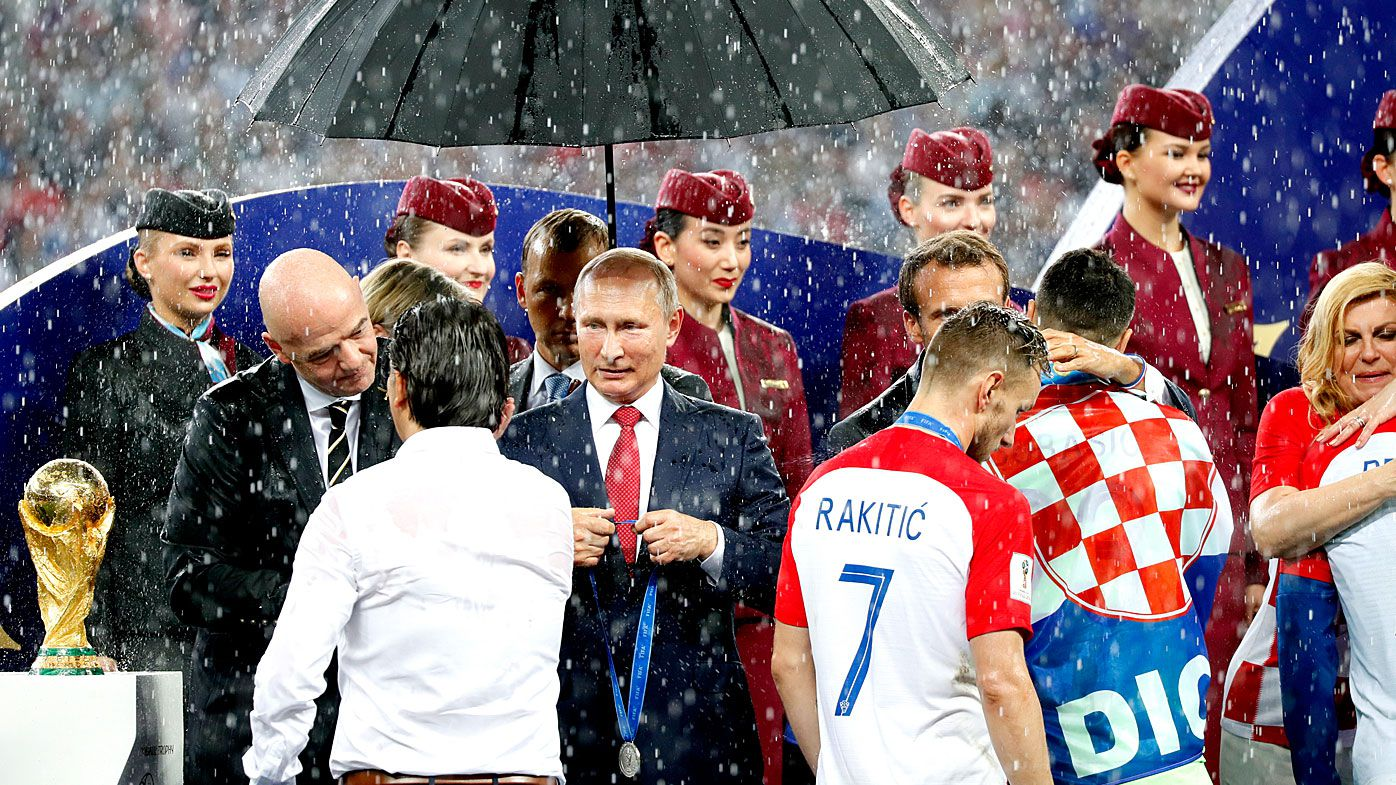 Vladimir Putin dry while world leaders soaked in wet World Cup trophy presentation